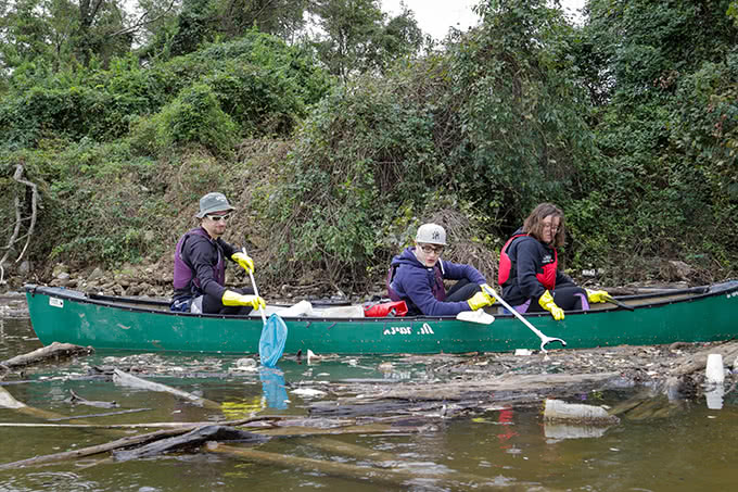 Students on canoe scooping water pollution