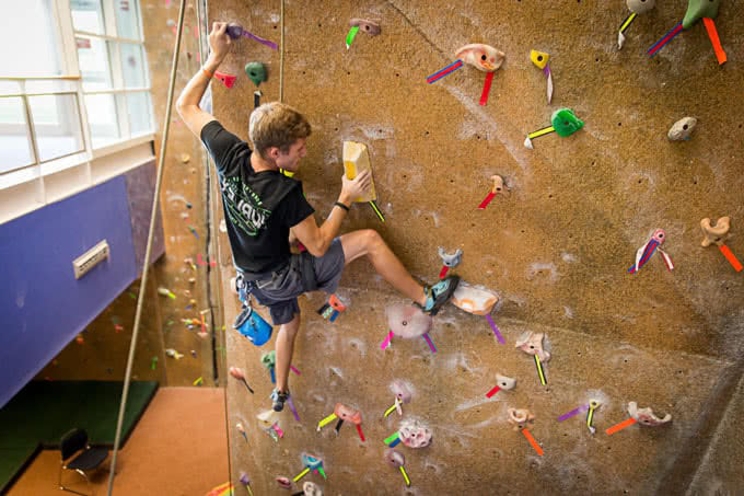 Student climbing on rock wall