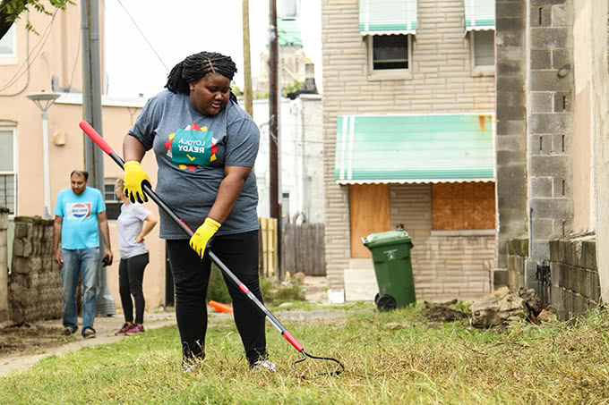 Student raking in vacant grassy lot