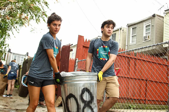 Students carrying garbage can in alley