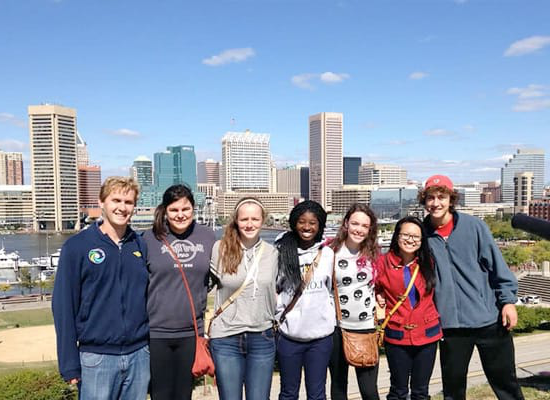 A group of students posing for a photo, with the harb要么 and 巴尔的摩 skyline in the background
