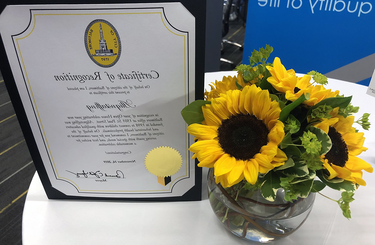 Photo of Certificate of Recognition from the City of Baltim要么e and a vase of sunflowers sitting on a table