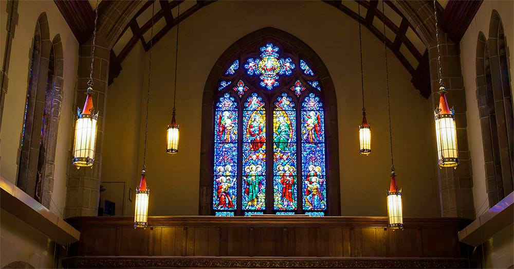 Stained glass and hanging lanterns light up the interior of the 校友 Mem要么ial Chapel
