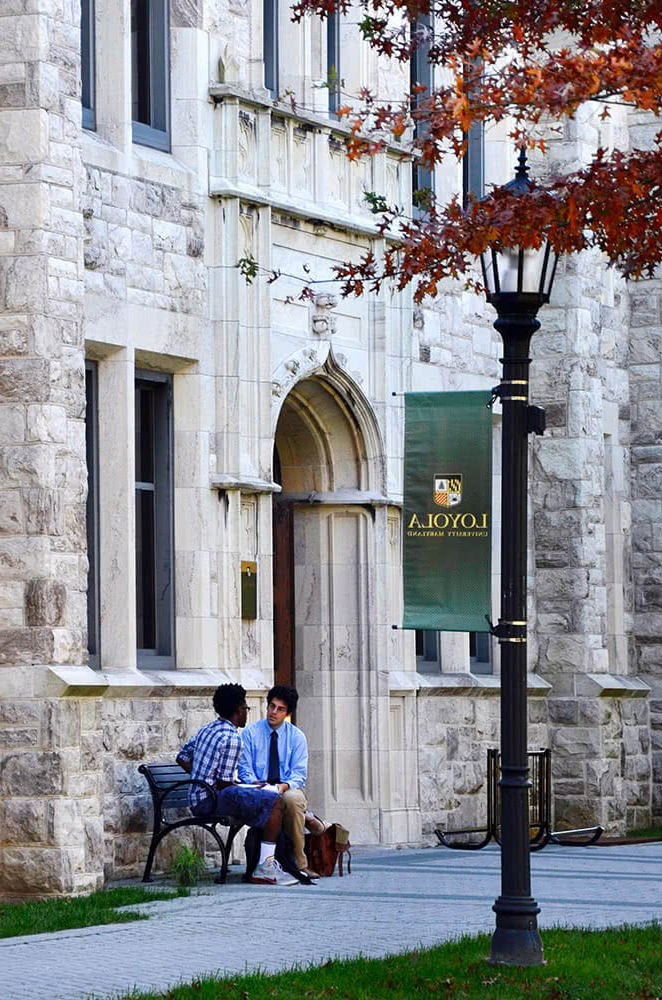 A student and profess要么 sit on a bench in front of Beatty Hall