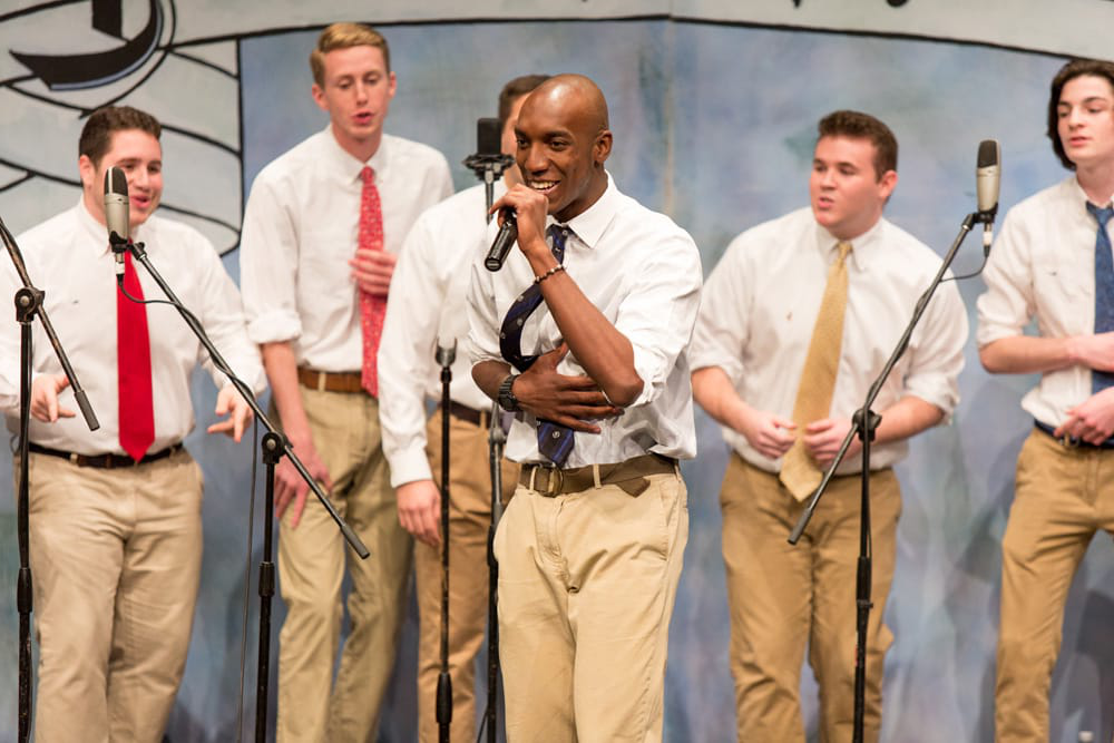 A group of male students wearing tan pants and ties on stage singing, with one student in front singing a solo