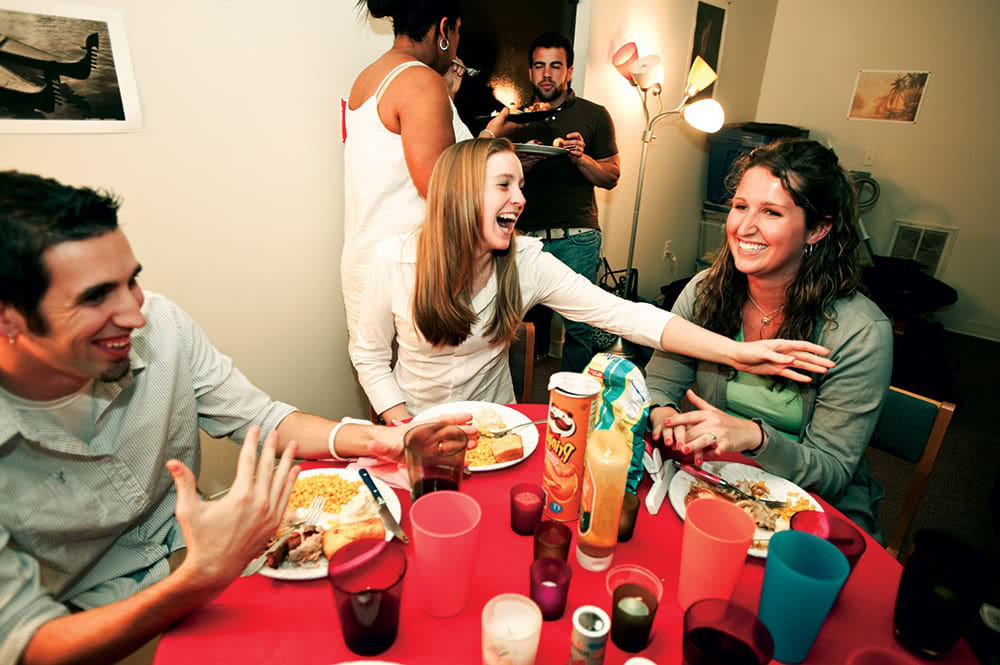 Students smiling and laughing around a table with a red tablecloth, food, plates, and drinks
