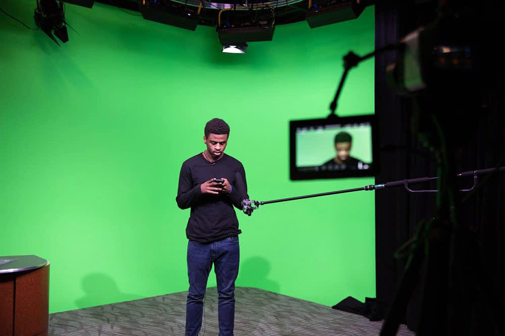 A student looking at a device while standing in front of a green screen