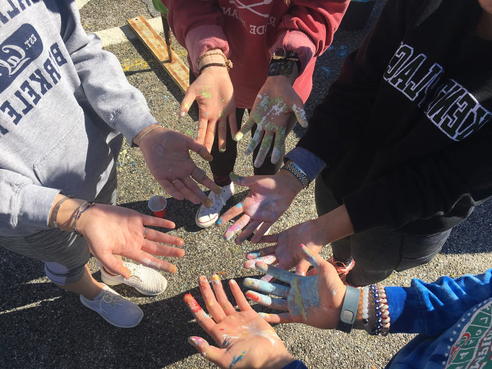 Students standing in a circle with their hands held out, covered in paint
