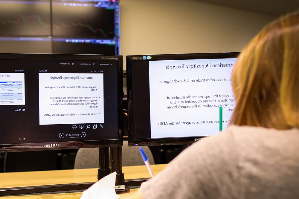 A view from behind of a student sitting in front of a computer screen, which displays information about American deposit要么y receipts