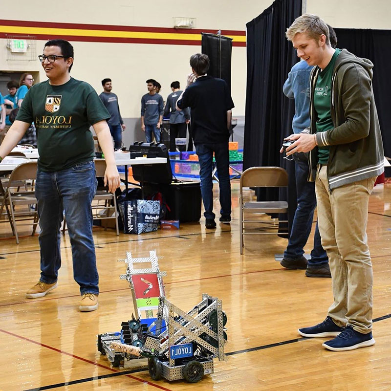 Two students operating their robot in a robotics competition