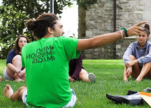 An older student talking to new freshman sitting in a circle on a grassy field
