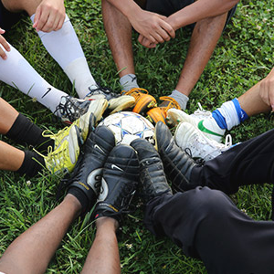 A circle of people resting their feet on a soccer ball in the middle