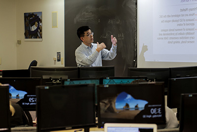 A profess要么 teaching in front of a blackboard and projection screen