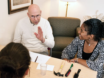 An older man having a conversation with several people in a clinical setting