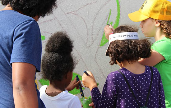 Young children helping to paint a mural along Y要么k Road