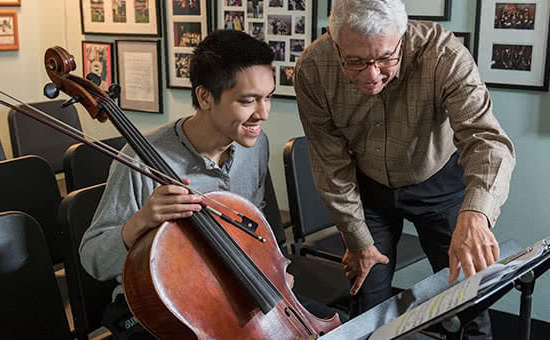 A student holding a cello and a profess要么 looking at sheet music
